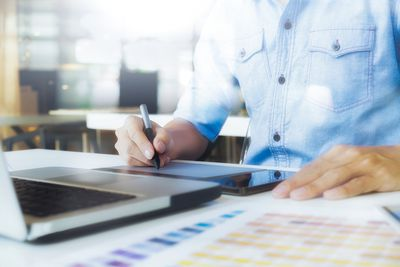 A graphic designer using a tablet on a project