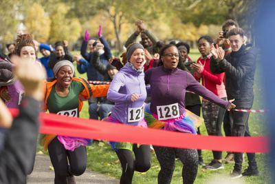 Enthusiastic female runners in tutus nearing finish line at charity run