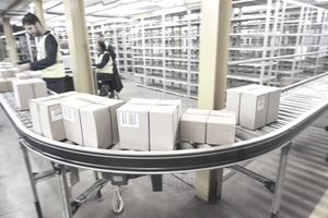 Workers processing boxes on conveyor belt in distribution warehouse