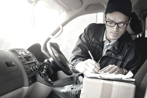 Shot of a courier making deliveries in his van and filling out paper on a clipboard.