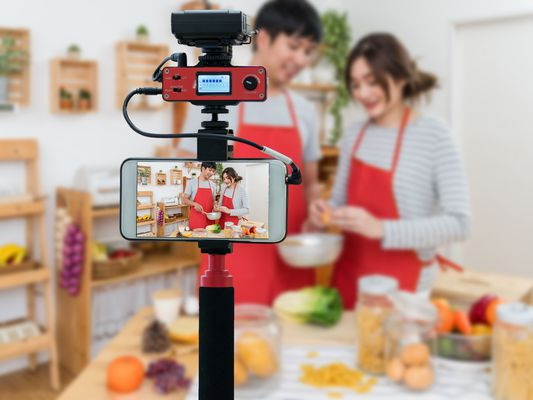 A young couple dressed in matching red aprons in the kitchen demonstrate kitchen technique before a tripod mounted camera.